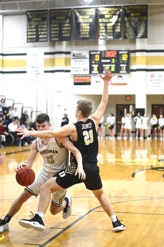 Upperman's Kason Grissom, left, drives the lane during the Bees' 89-33 rout of DeKalb County Tuesday night in Baxter.