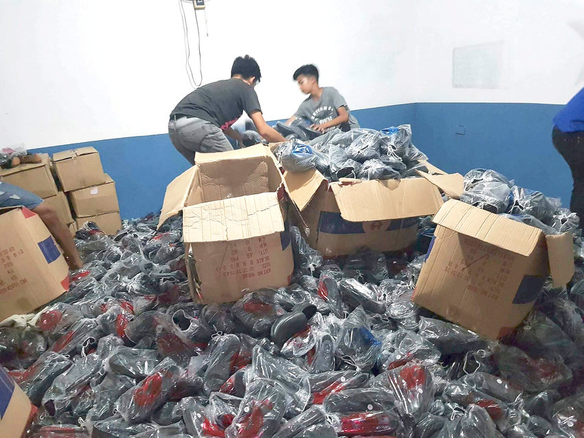 Volunteers in the Philippines sort through boxes of shoes donated as part of a program sponsored by Kenneth Hargis of Cookeville.
