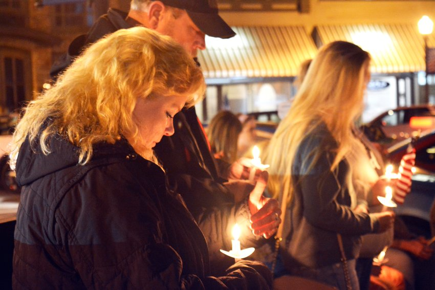 Anissa Spicer prays at the candlelight vigil Tuesday night at the Putnam County Courthouse Square.