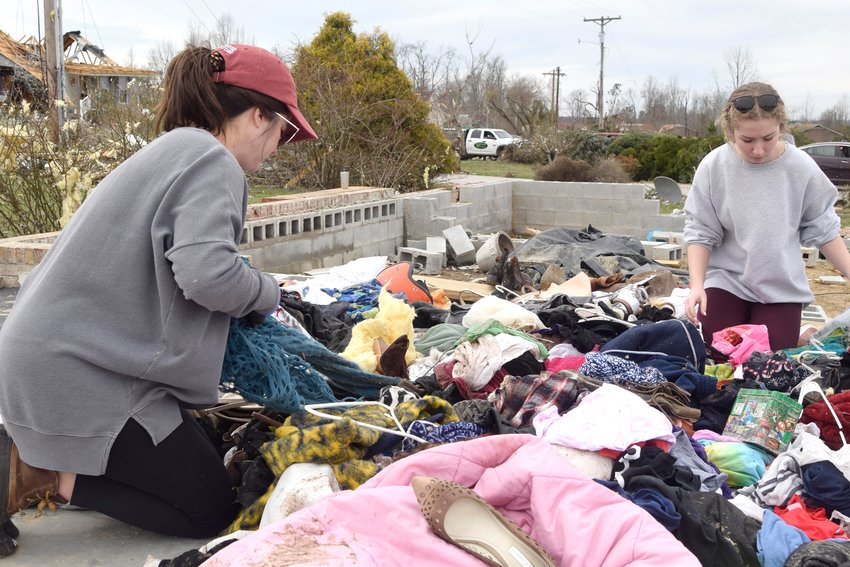 Rachel McCormick and her daughter, Ella, sort through clothing and shoes that can be salvaged from the home of Rachel's sister-in-law, Tracy Savage on Herald Court Wednesday.