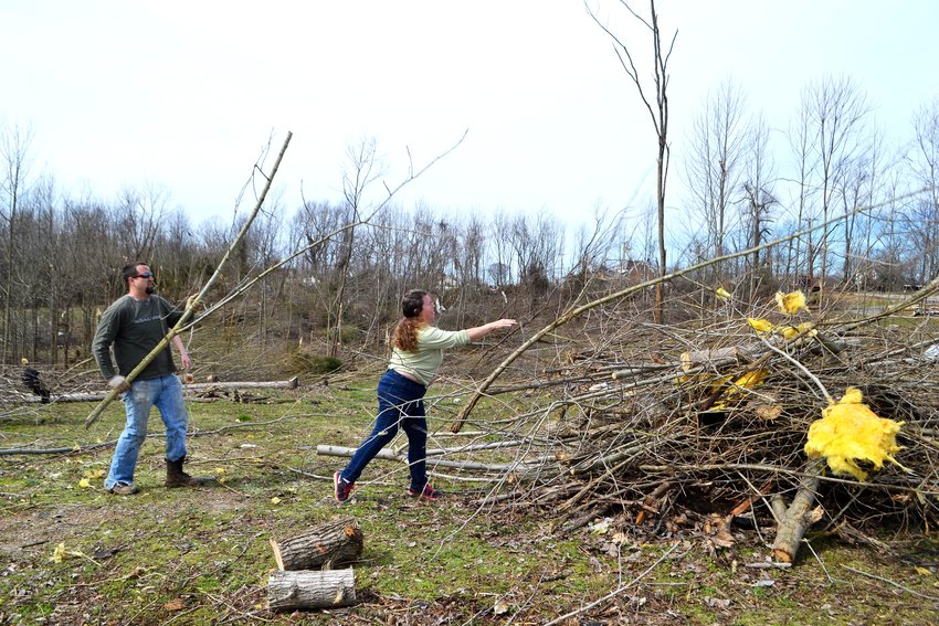 Kevin McCaleb and Kendra Mahan removed brush Wednesday from property along West Broad Street.
