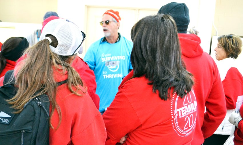 Tornado cleanup volunteers from Averitt Express listen to a safety briefing before heading out Saturday.