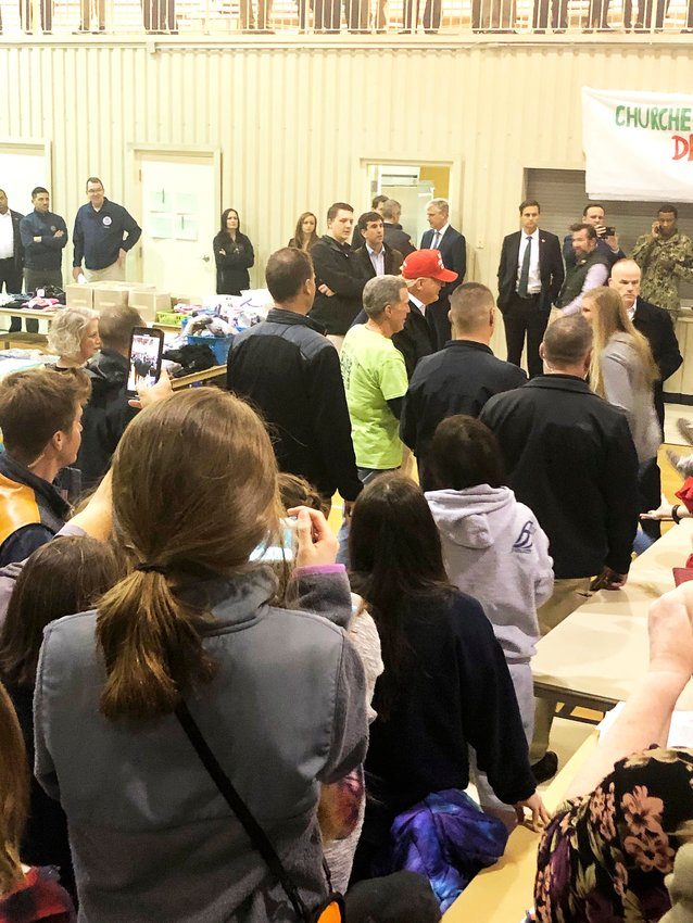President Donald Trump, in the red hat, poses for a photo with Jefferson Avenue Church of Christ disaster relief coordinator Rick Gilbert in the church's gym, the relief distribution center, Friday.