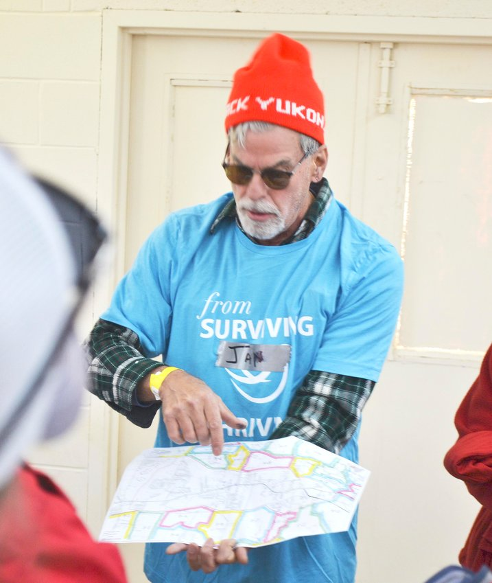 Jan Arnson looks over a map of the disaster area during a safety briefing with volunteers Saturday.