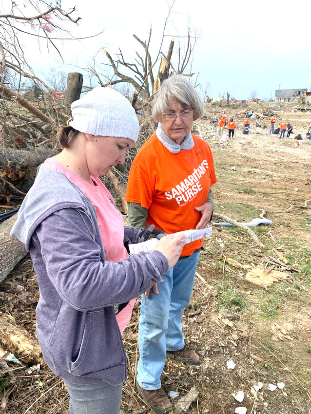 Amy Jennings, left, holds the life insurance policy of Keith and Cathy Selby, who died in the tornado in Putnam County last week.