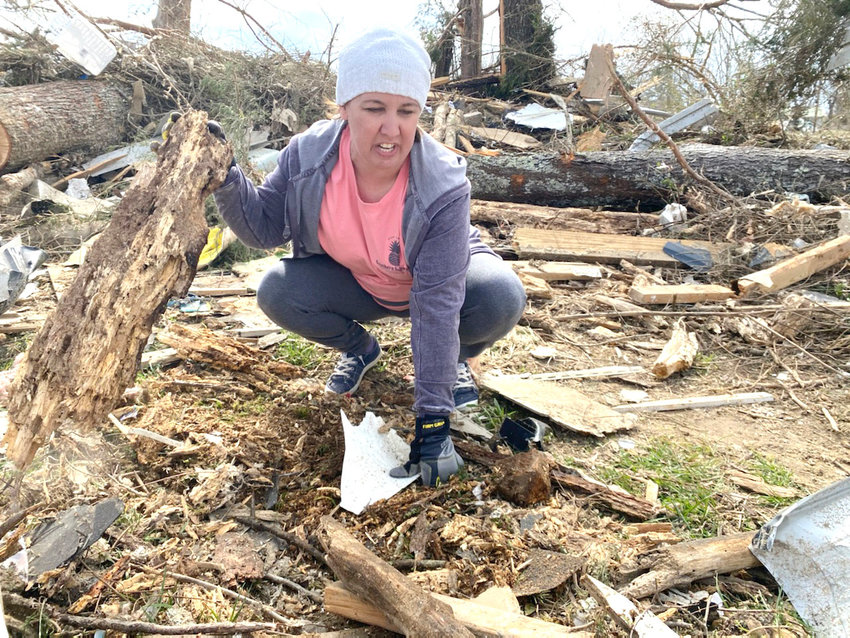 Amy Jennings, one of the survivors of last Tuesday's tornado, sifts through debris hoping to find Harper Mynatt's 'lovie,' a small blanket with a stuffed bear head on top.