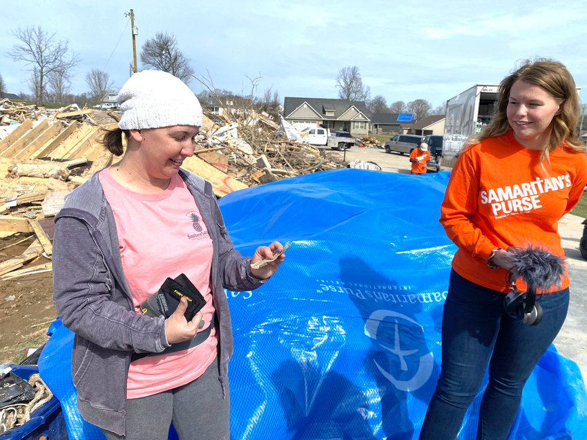Amy Jennings, left, holds a $20 bill found on the site of the Mynatt home on Hensley Drive with Alyssa Benson of Samaritan's Purse.