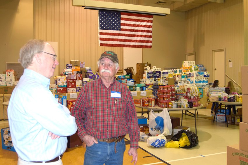 U.S. Rep. John Rose of Cookeville and Doug Fowler, elder at Jefferson Avenue Church of Christ, talk next to the mountain of donations for tornado victims that have been collected so far at the church. The relief center will be open for those seeking help as well as a place to drop off donations from 9 a.m. to 8 p.m., Monday through Saturday and 1 to 6 p.m. on Sunday.