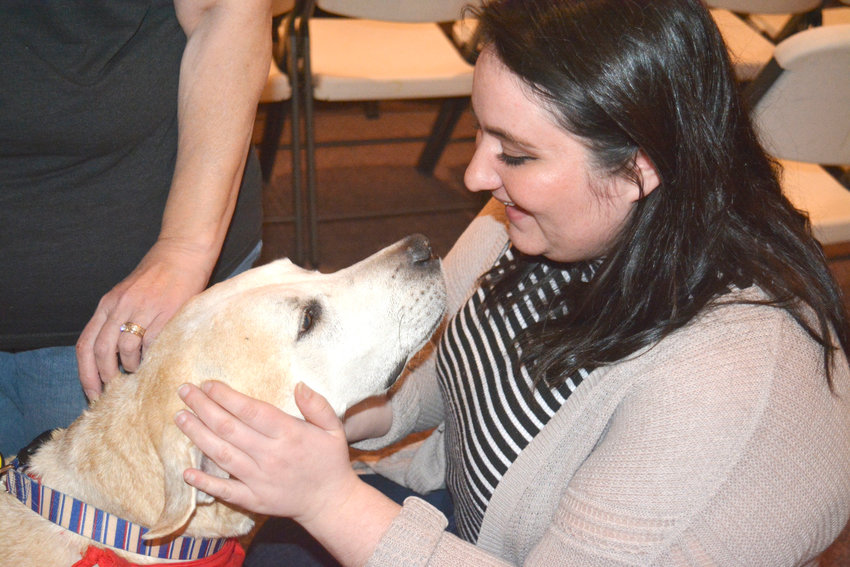 Service dogs were available during the Community Debriefing Wednesday. Liz Dewar gives love to Bear.