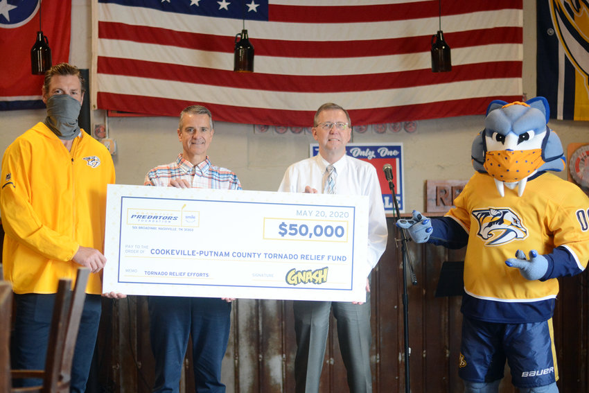 The Nashville Predators' (from left) Hal Gill presents Cookeville Mayor Ricky Shelton and Putnam County Mayor Randy Porter with a tornado relief check for $50,000, accompanied by Preds mascot Gnash, Wednesday at Red Silo Brewing Company.