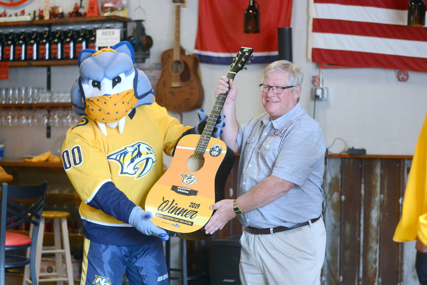 Nashville Predators mascot Gnash, left, presents a commemorative guitar for winning their craft beer festival  to Red Silo's Mark van der Bleek Wednesday at Red Silo.