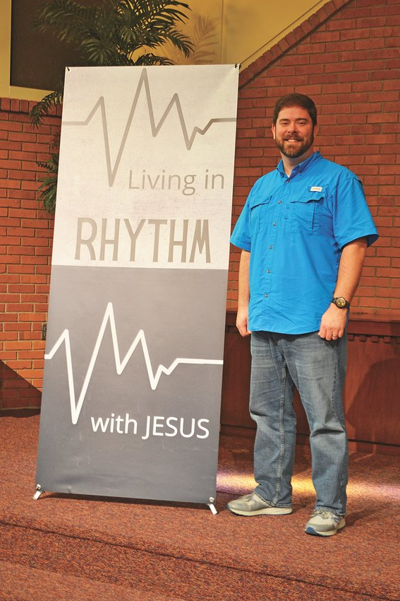 """Jefferson Avenue Church of Christ minister Andy Brewster stands before a sign about """"Living in Rhythm with Jesus."""""""