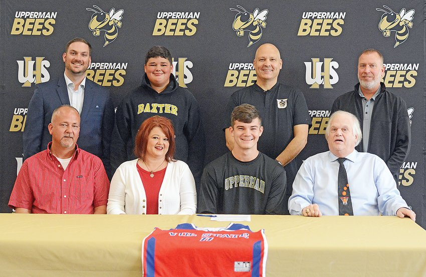 Former Upperman basketball player Kason Grissom, center, signs his national letter of intent with, front row from left, father Matt Grissom, mother Tracey Grissom, Vol State head coach Rusty Melvin, back row from left, UHS athletic director Nathan Brown, brother Kolton Grissom, UHS head coach Bobby McWilliams and UHS principal Billy Stepp.