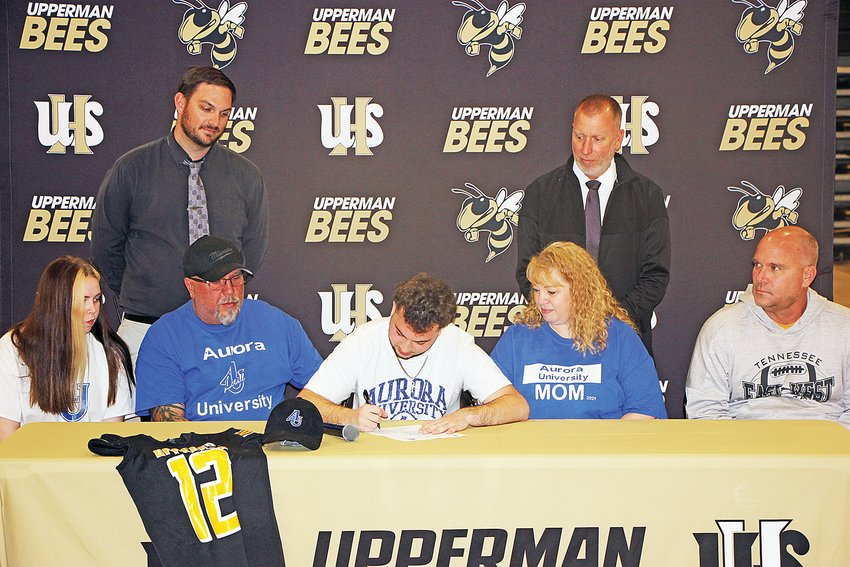 Upperman's Dalton Barney, center, signs his national letter of intent with, front row from left, sister Cassy Barney, father Kelly Barney, mother Kelly Barney, UHS head coach Adam Caine; back row from left, UHS athletic director Nathan Brown and UHS principal Billy Stepp.