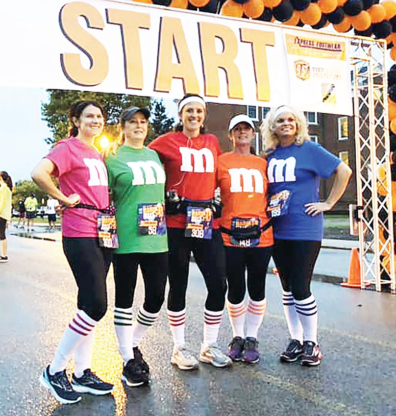 Runners dressed as M&M candies pose at the starting line for a previous Haunted Half Marathon.