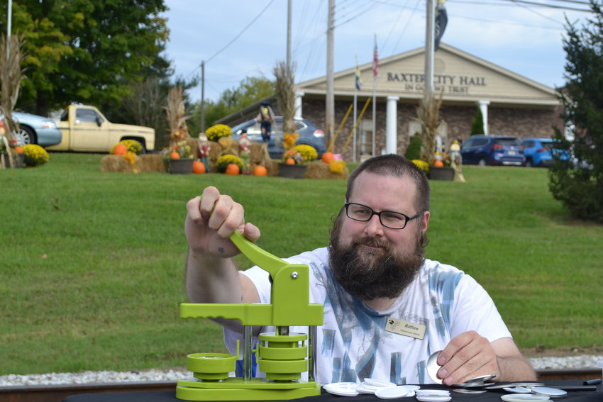 Baxter Branch Library Director Matthew Krist makes a stamp at one of the stations along the path of the Baxter Harvest Festival Saturday.