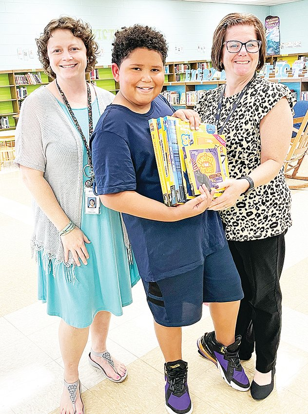 Former Cane Creek Elementary student DeShawn Wester felt called to pay it forward when he won a set of books valued at over $100. He knew the books would be loved and read over and over in the library at Cane Creek Elementary, so he donated them to the school. From left are Cane Creek librarian Laura Roberson, DeShawn Wester, and PreK teacher Maria Green.