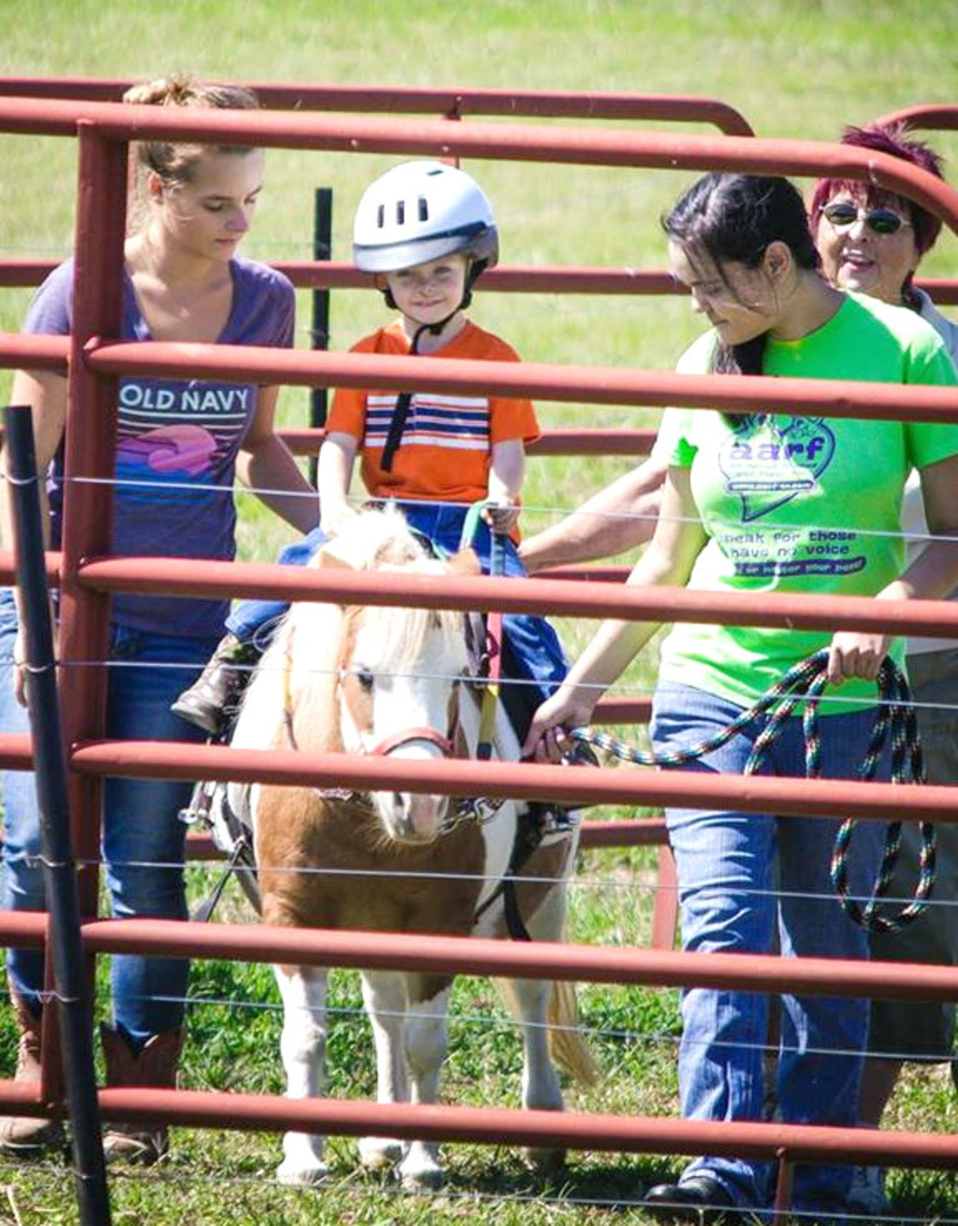 Isaac Snell takes his first ride on Buttercup the pony in the round pen assisted by, from left, Macy Coomer, side-walker; Rachel McCormick, leader; and Bobbie Abell, side-walker.