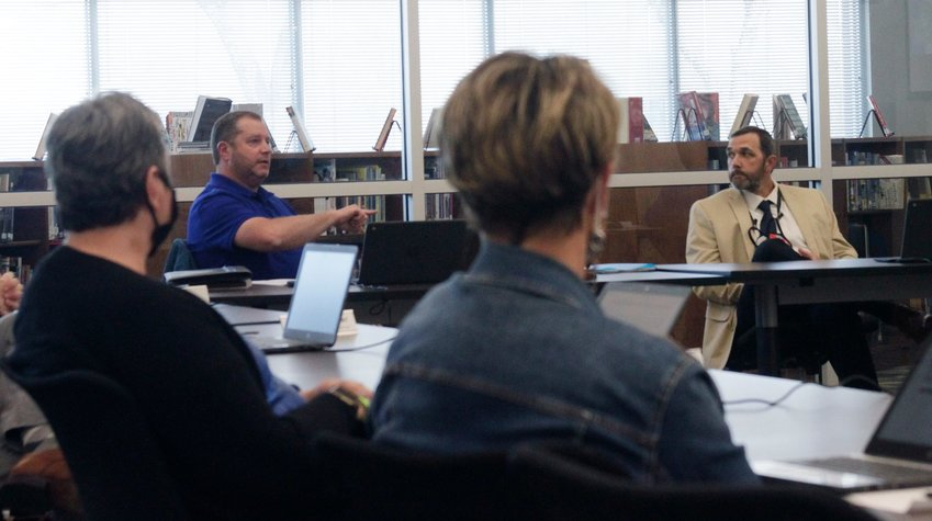Moberly Public Schools Superintendent Dr. Dustin Fanning turns his head to listen to Bobby Riley, school board president, issue a statement during the district's Board of Education business meeting held at the high school.