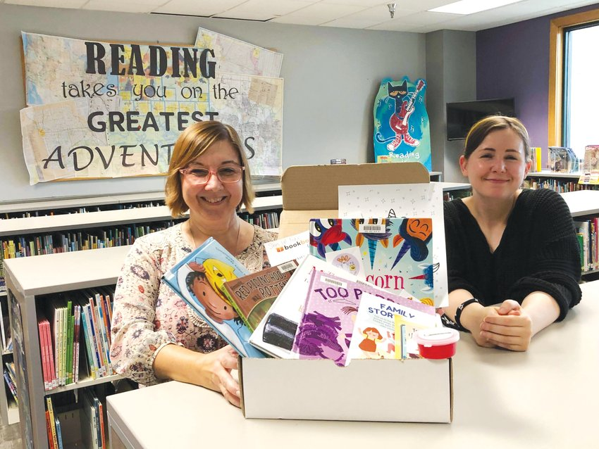 Melissa Wetzel and Robin Fara, Little Dixie Regional Libraries staff, share the new youth book box service with patrons at the local library.