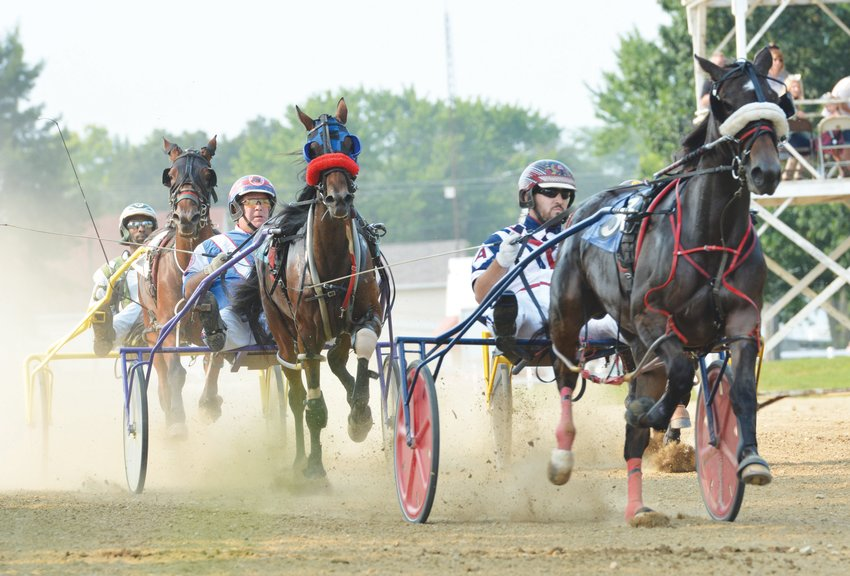 Wyatt Avenatti, right, leads the field heading into the first turn during Monday night's first harness race at the Edgar County Fair.  As the race progressed, Avenatti maintained his lead before going on to earn his first career win with his pacer Mommy Said Nonono. Also pictured,  left to right), are Cornelius Cavett steering Aniemaybombay and Chris Brown guiding Ryan's Shark Attack. Not pictured is Darla Martin Lohman and her horse Ellis Gray.